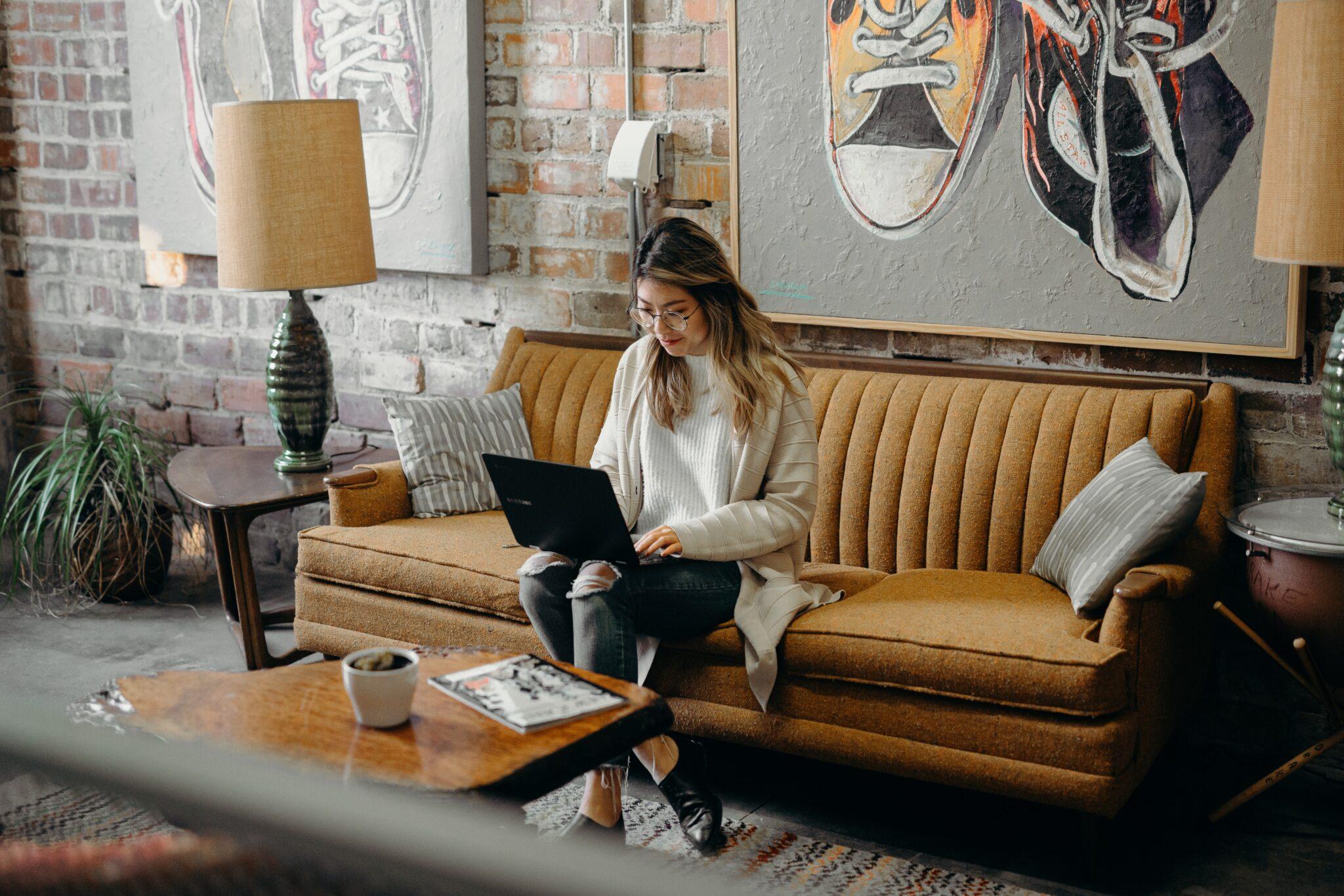 Woman using laptop while sitting on sofa